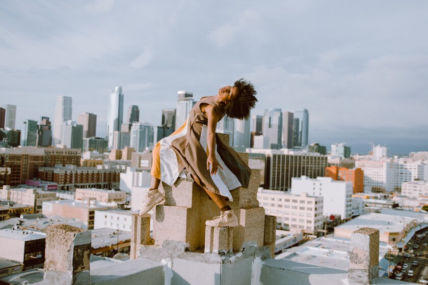 A dancer with the L.A.-based Heidi Duckler Dance appears to hover over downtown rooftops.