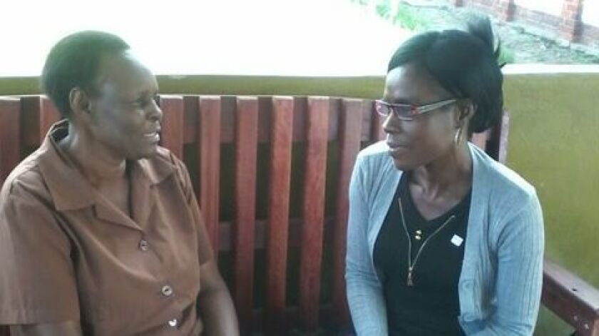 "A Zimbabwean ""grandmother,"" left, talks to a patient in the Friendship Bench program."