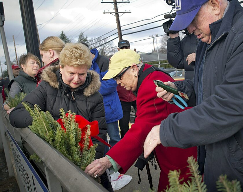 Rep. Carolyn McCarthy, D-NY, center in the red coat, and Joyce Gorycki, center left, hang wreaths at the Long Island Rail Road station in Garden City, N.Y., Saturday, Dec. 7, 2013 to commemorate the 20th anniversary of the shooting rampage that took the lives of both of their husbands aboard a Long Island Rail Road commuter chain. On Dec. 7, 1993, deranged gunman Colin Ferguson opened fire on the crowded train, killing six and wounding 19 before being subdued by commuters as he paused to reload. McCarthy's son, who was also riding on the train, was seriously wounded. (AP Photo/Newsday, J. Conrad Williams, Jr.) NYC OUT, NO SALES