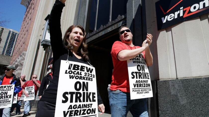 Verizon workers picket outside one of the company's facilities in Boston on April 13.