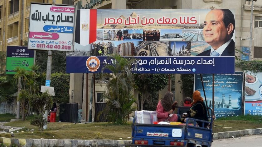 On Jan. 22, 2018, Egyptians drive past a billboard bearing the image of Egyptian President Abdel Fattah Sisi, who is seeking reelection.
