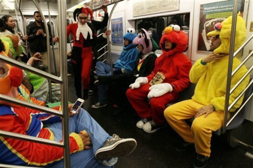 FILE - This Nov. 1, 2011 file photo shows a group of friends dressed as Sesame Street characters after attending the Village Halloween Parade in New York. From the wrath of nature to the wrath of young children: From Maryland to Kentucky to Maine, Halloween festivities were being canceled or postponed. The most high-profile postponement was that of New York's huge parade in Greenwich Village, with its outlandish floats and millions of revelers, mainly adults. Mayor Michael Bloomberg said the city's police were simply too taxed with Sandy's aftermath. (AP Photo/Tina Fineberg, file)