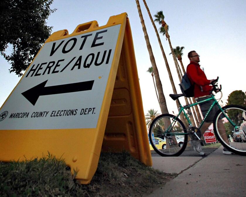 A sign directs voters to a polling station in Tempe, Ariz.