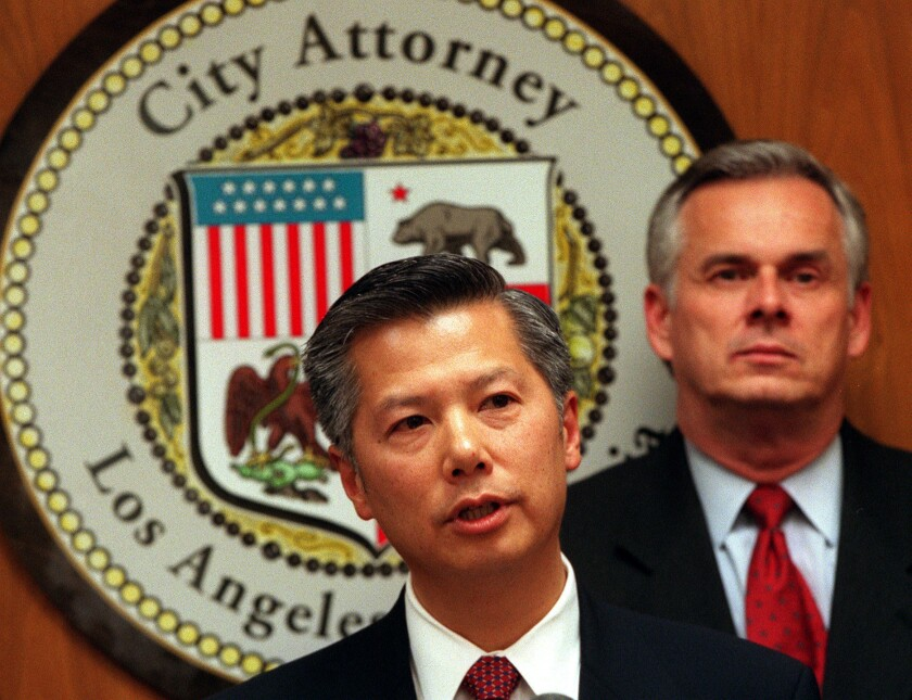 Then-Assistant Atty. Gen. Bill Lann Lee, left, head of the U.S. Justice Department's Civil Rights Division, is joined by former Los Angeles City Atty. Jim Hahn at a news conference in November 2000 after the L.A. City Council's approval of the LAPD consent decree.