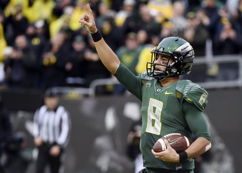 FILE - In this Nov. 22, 2014, file photo, Oregon quarterback Marcus Mariota (8) celebrates after scoring a touchdown during the first quarter of an NCAA college football game against the Colorado in Eugene, Ore. Mariota is The Associated Press college football player of the year. He won the AP vote
