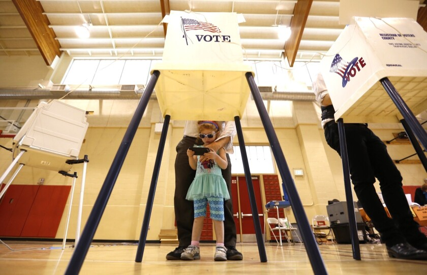 """A girl waits for her father to finish voting in Van Nuys on June 7. Donald Trump has raised the possibility of the """"rigged"""" election."""
