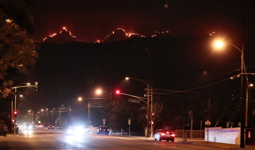 The Bobcat Fire smolders in the mountains above Monrovia Thursday.
