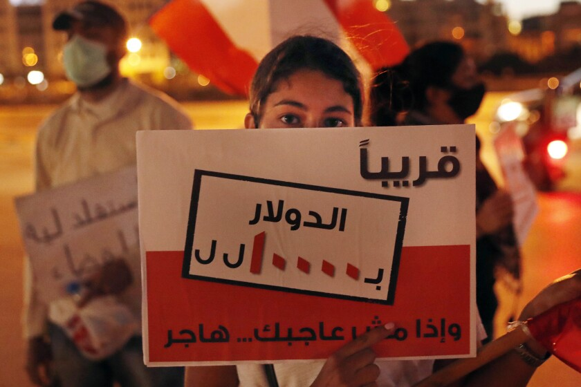 """An anti-government protester holds a placard in Arabic that reads """"Soon $ 1 = 10000 Lebanese pounds, if you are not happy, immigrate,"""" during a protest against the political leadership they blame for the economic and financial crisis, in front of the government house in downtown Beirut, Lebanon, Thursday, June 11, 2020. (AP Photo / Hussein Malla)"""