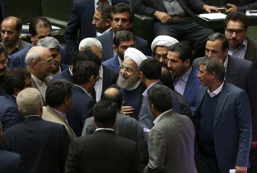 Iranian President Hassan Rouhani is surrounded by lawmakers after a speech in parliament on Sunday.