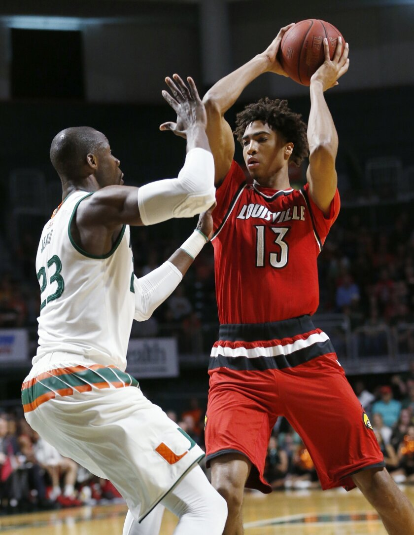 Louisville forward Raymond Spalding (13) looks for an open teammate past Miami center Tonye Jekiri (23) during the first half of an NCAA college basketball game, Saturday, Feb. 27, 2016, in Coral Gables, Fla. (AP Photo/Wilfredo Lee)