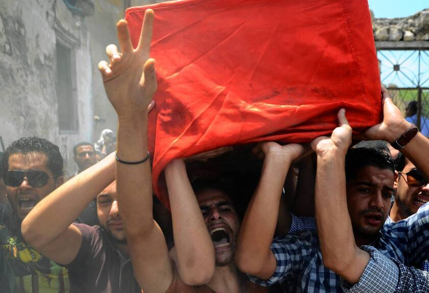 Mourners in Alexandria, Egypt, carry the coffin of a police officer killed in clashes between protesters and security forces.