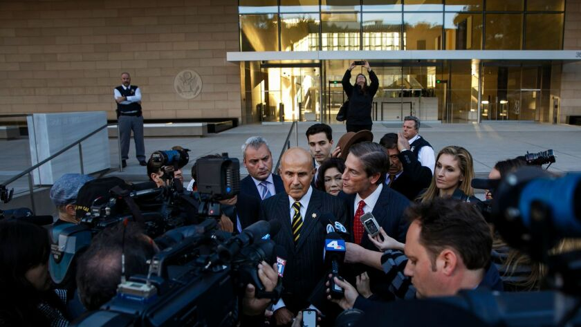 Former Los Angeles County Sheriff Lee Baca, center, talks to reporters outside court in December.