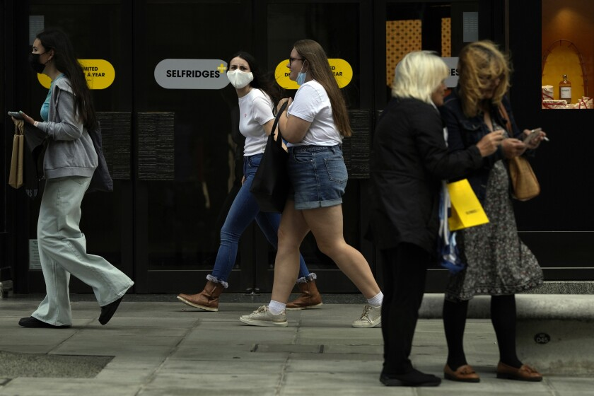 Two women walk along Oxford Street while wearing a face masks against the coronavirus in London, Friday, Aug. 6, 2021. The number of covid positive tests for August 5, the latest available figure show the United Kingdom had just over 30,000 confirmed infections. (AP Photo/Alastair Grant)