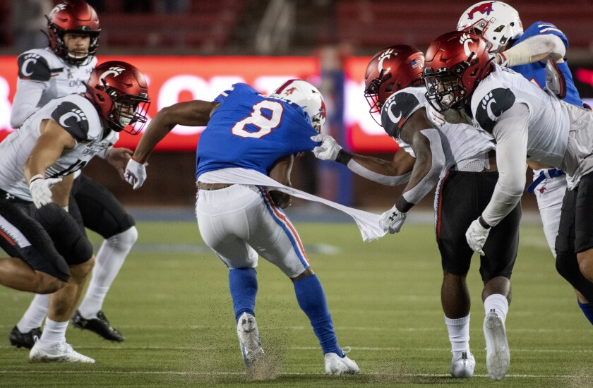 Cincinnati's Jaheim Thomas grabs the shirt of SMU kick returner Bryan Massey (8) on a kickoff return during the second half of an NCAA college football game Saturday, Oct. 24, 2020, in Dallas. Cincinnati won 42-13. (AP Photo/Jeffrey McWhorter)