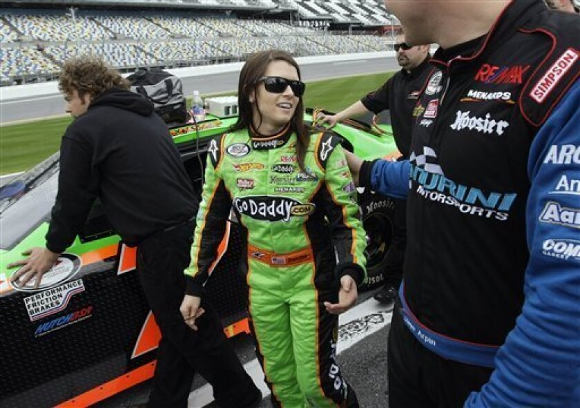 Driver Danica Patrick talks with ARCA driver Steve Arpin as she waits for her turn to qualify for the Lucas Oil Slick Mist 200 ARCA auto race at the Daytona International Speedway in Daytona Beach, Fla., Friday, Feb. 5, 2010. (AP Photo/Dave Martin)