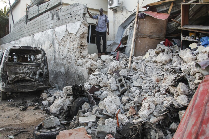 A hotel security guard stands by wreckage in the aftermath of an attack on the Afrik hotel in Mogadishu, Somalia, Monday, Feb. 1, 2021. At least five people have died in the attack on the Mogadishu hotel by Somalia's al-Shabab rebels that was ended early Monday by security forces, according to the Somali police force. (AP Photo/Farah Abdi Warsameh)
