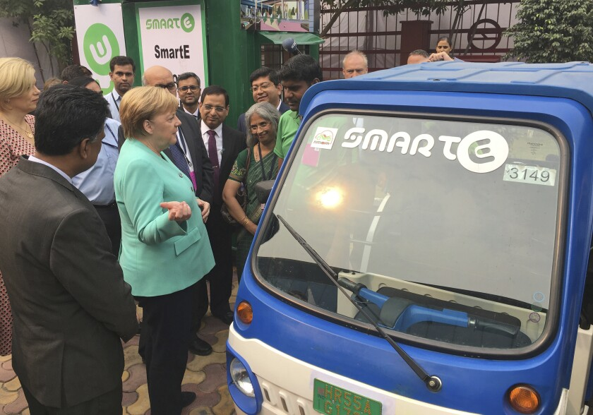 German Chancellor Angela Merkel speaks with a driver of an electric vehicle at a metro station in New Delhi, India, Saturday, Nov. 2, 2019. India and Germany agreed on Friday to enhance cooperation in tackling climate change, cybersecurity, skill development, artificial intelligence, energy security, civil aviation and defense production. The two countries signed several agreements, with Prime Minister Narendra Modi saying India is eager to benefit from Germany's expertise. (AP Photo/Shonal Ganguly)
