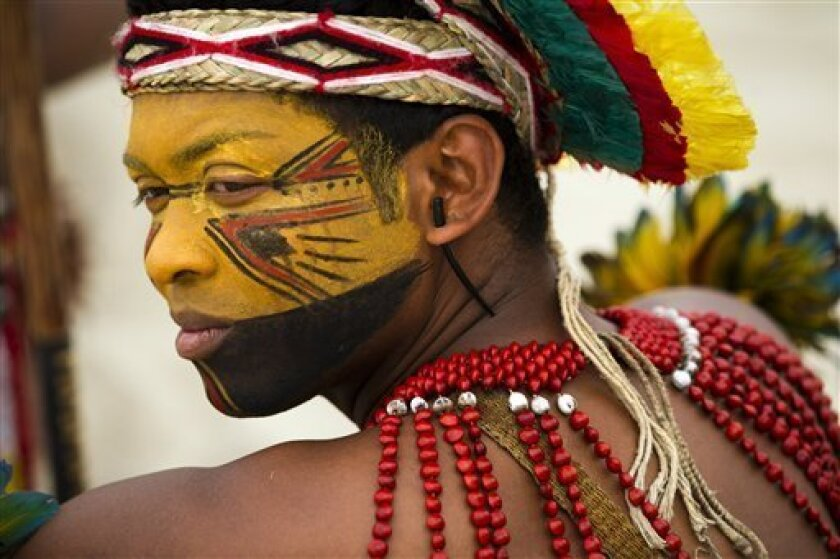A Pataxo Indian waits to participate in the building of a human banner on Flamengo beach, organized by Amazon Watch, on the sidelines of the Rio+20, or UN Conference on Sustainable Development in Rio de Janeiro, Brazil, Tuesday, June 19, 2012. The activists are calling attention to threats posed to