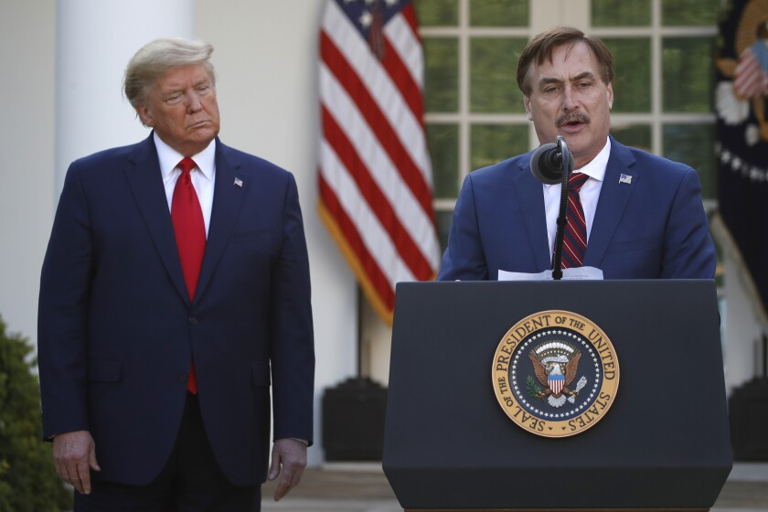 My Pillow CEO Mike Lindell, right, speaks as President Trump listens during a briefing about the coronavirus in March.