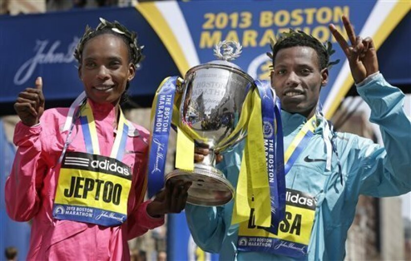 Rita Jeptoo of Kenya and Lelisa Desisa of Ethiopia pose with a trophy at the finish line after winning the women's and men's divisions of the 2013 Boston Marathon in Boston Monday, April 15, 2013. (AP Photo/Elise Amendola)
