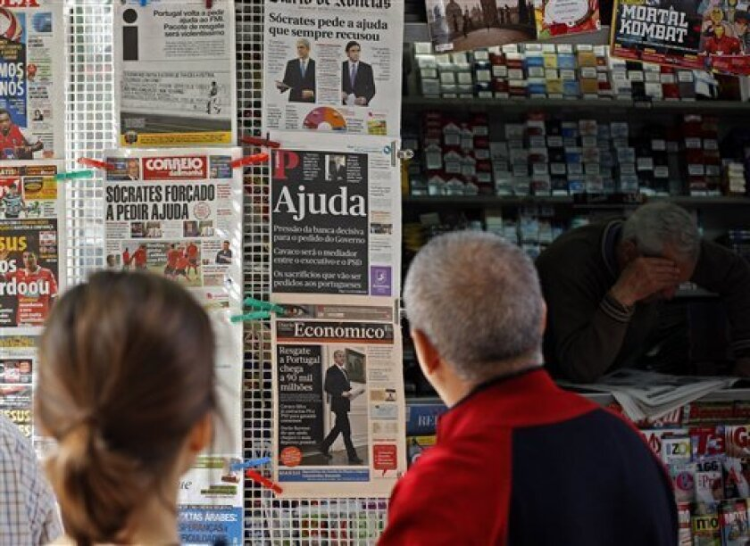 People look at newspapers' frontpages, some with pictures of Prime Minister Jose Socrates, Thursday, April 7, 2011, in Lisbon. Socrates announced late Wednesday that Portugal will ask for a bailout to relieve its crushing debt, joining Greece and Ireland by becoming the third eurozone nation to seek outside help amid a bruising financial crisis. (AP Photo/ Francisco Seco)