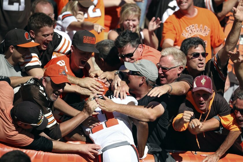 Cleveland Browns fans mob Browns' Travis Benjamin after he scored in the second half of an NFL football game against the Tennessee Titans, Sunday, Sept. 20, 2015, in Cleveland. The Browns won 28-14. (AP Photo/Ron Schwane)