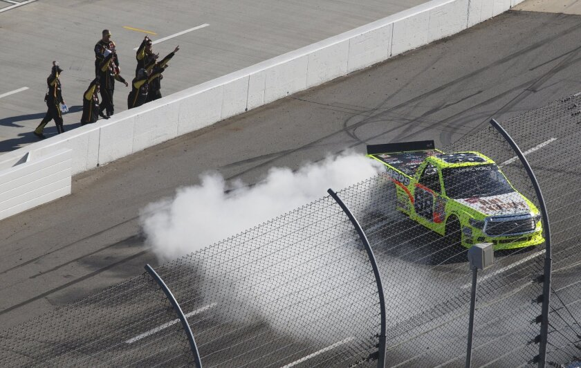 Camping World Truck Series driver Matt Crafton (88) celebrates winning the NASCAR Camping World Truck auto race with his team as he does a burnout at the Martinsville Speedway in Martinsville, Va., Saturday, Oct. 31, 2015.    (AP Photo/Steve Sheppard)
