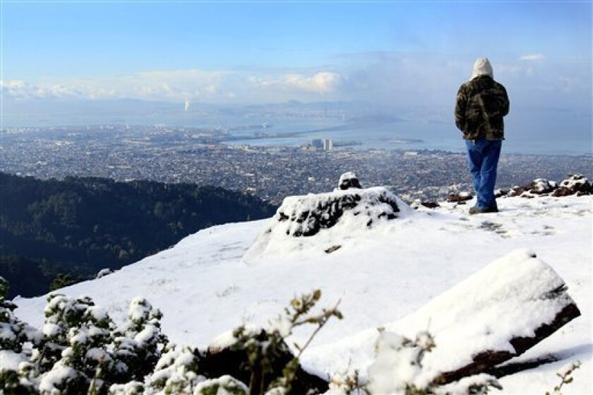 Carlos Belasco of Livermore stopped along Grizzly Peak Blvd. on the snow-covered ridge to admire the view of the Bay, San Francisco and the East Bay after a cold Arctic storm blanketed the Oakland-Berkeley hills with several inches, Monday, Dec. 7, 2009 in Berkeley, Calif. (AP Photo/Dino Vournas)