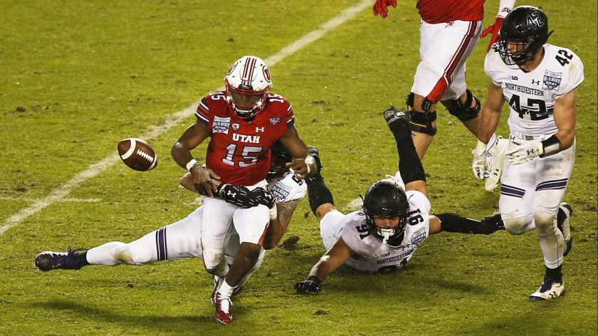 Northwestern's Joe Gaziano forces a fumble against Utah quarterback Jason Shelley. Jared McGee ran it back 82 yards for a touchdown in the Wildcats' wild Holiday Bowl comeback Monday at SDCCU Stadium.
