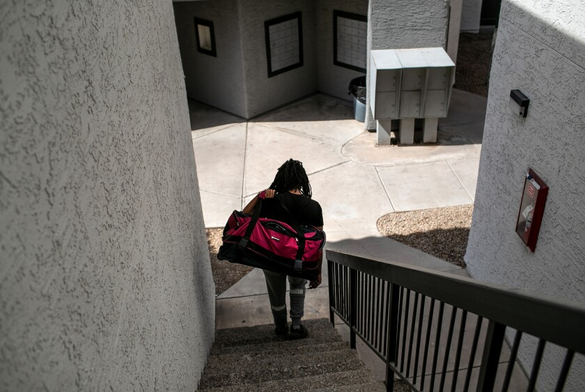 An apartment resident carries out a bag of clothing while being evicted for non-payment of rent