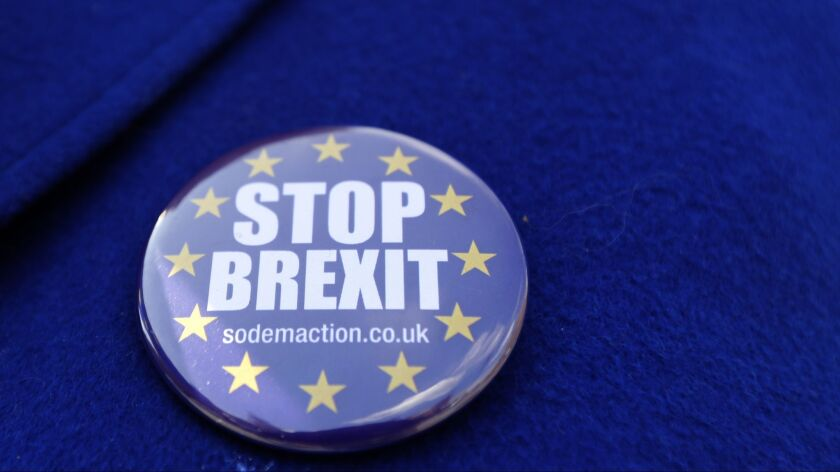 A badge is worn by a pro-EU demonstrator outside Parliament in London, Wednesday, June 13, 2018. The