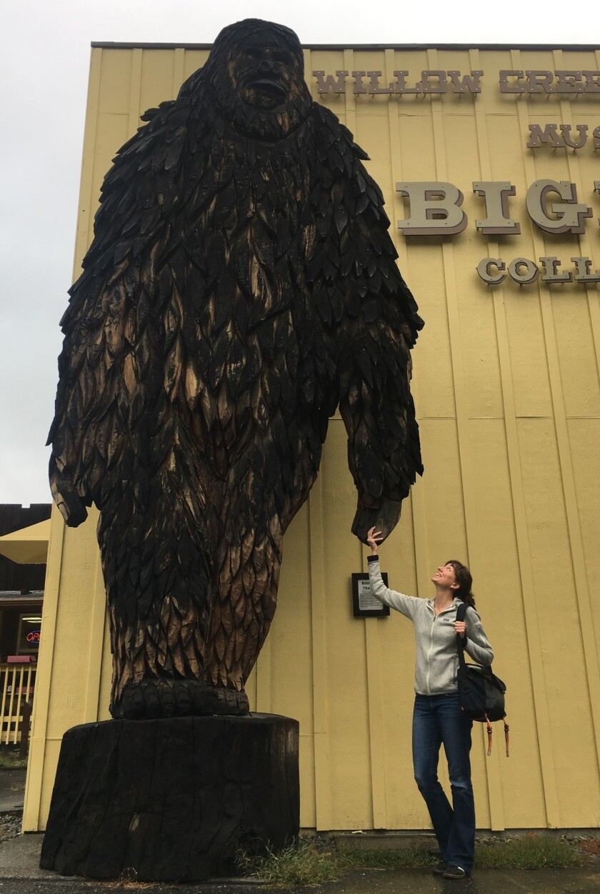 Laura Krantz holds hands with the 20-foot carved wooden Bigfoot that stands outside the entrance to the Willow Creek-China Flat Museum in Willow Creek, Calif., at the 50th anniversary celebration of the 1967 Patterson-Gimlin film.