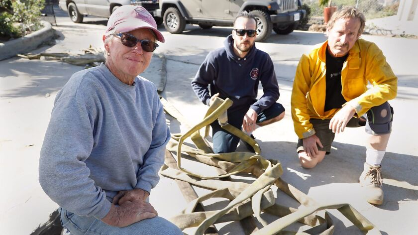 Three former firefighters with two old fire hoses saved five homes on Redondo Drive in Bonsall from burning down Thursday night. Cathy Orchard, 58, Todd Smith, 34, and Don Philippbar pose with one of the hoses on Friday morning.