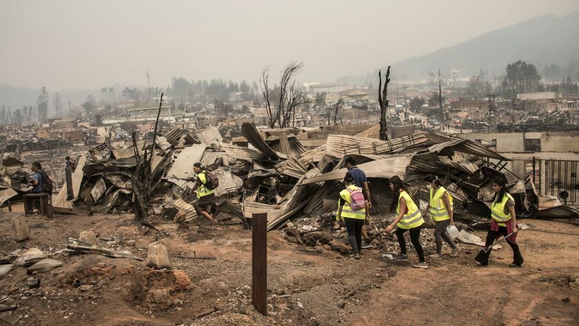 An emergency team walks through the remains of Santa Olga, Chile, about 200 miles south of Santiago, after the area was devastated by a wildfire.