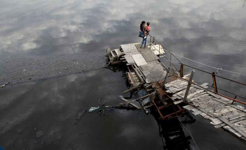 In this Nov. 18, 2013 photo, a woman holds a girl in her arms while standing on a dock at the Riachuelo river in La Boca neighborhood of Buenos Aires, Argentina. Although the odor of the brown-gray river can be overpowering, the historic neighborhood, which is known as a tango hotspot and home of t