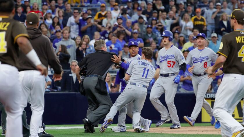 Los Angeles Dodgers manager Dave Roberts, center, is held back by Los Angeles Dodgers third baseman Logan Forsythe as the Dodgers and the San Diego Padres come onto the field during an argument June 30, 2017, in San Diego.