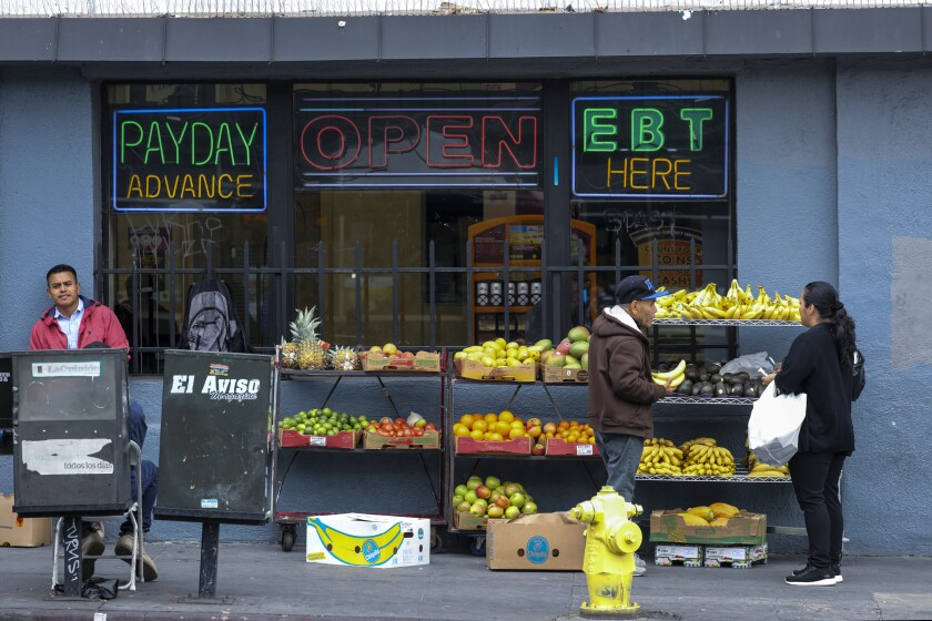 A fruit vendor goes by the routine business on 7th. and Alvarado on Monday March 16, 2020 in Los Angeles. In Los Angeles, bars and nightclubs have closed and restaurants have halted dine-in service and limited their business to takeout orders until March 31, following an order from Mayor Eric Garcetti.