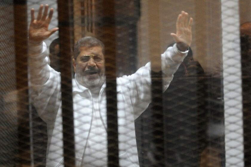 Ousted President Mohamed Morsi waves from the defendants' cage during his January trial at the police academy in Cairo.