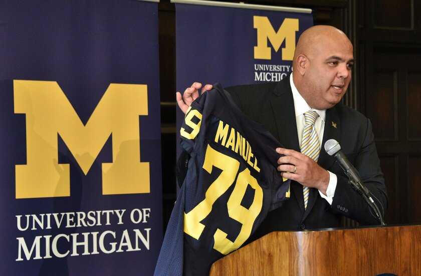 Michigan's new athletic director Warde Manuel holds up a jersey during a news conference, Friday, Jan. 29, 2016, at the Student Union in Ann Arbor, Mich. The 47-year-old Manuel, who had been Connecticut's athletic director since 2012, was given a five-year deal by Michigan. The salary was not immediately disclosed. (Dale G. Young/Detroit News via AP) DETROIT FREE PRESS OUT; HUFFINGTON POST OUT; MANDATORY CREDIT
