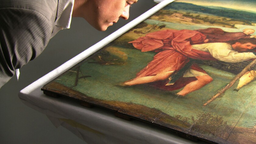 """In a scene from the documentary """"Hieronymous Bosch: Touched by the Devil,"""" art historian Matthijs Ilsink examines the painting """"Saint Christopher."""""""