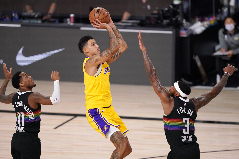 Lakers guard Kyle Kuzma shoots between Denver Nuggets' Monte Morris and Torrey Craig.