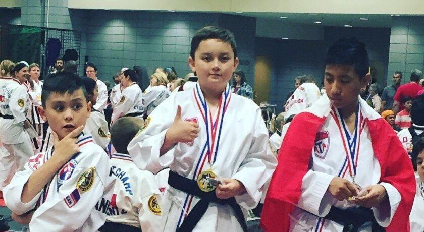 Gavin Robinson, middle, stands on the podium after winning the 9-10 age-group world championship in first-degree sparring on July 1 at the American Taekwondo Association Tournament of Champions in Little Rock, Arkansas.