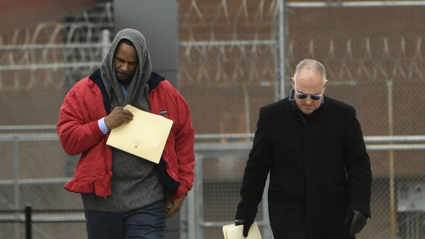Singer R. Kelly left, walks with his attorney Steve Greenberg right, after being released from Cook