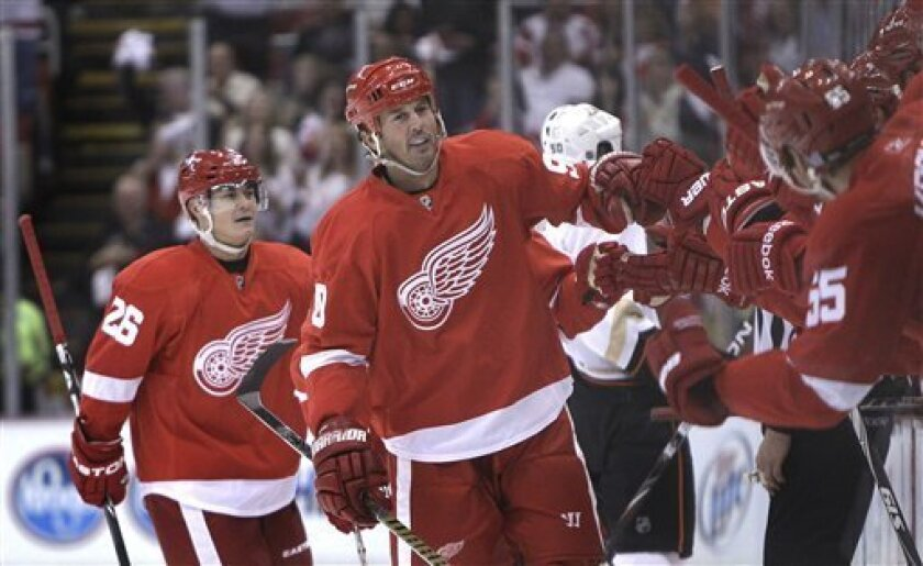 Detroit Red Wings center Mike Modano (90) is congratulated by teammates after a goal during the first period of an NHL hockey game against the Anaheim Ducks in Detroit, Friday, Oct. 8, 2010. (AP Photo/Carlos Osorio)