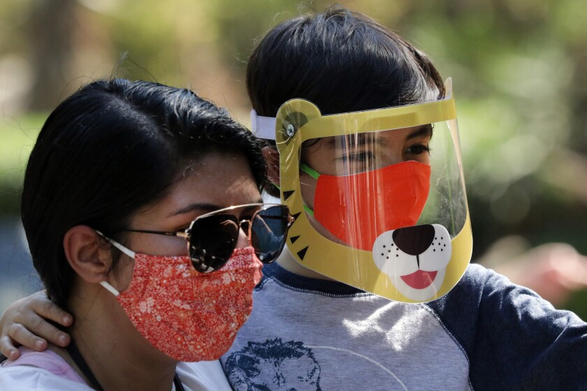 A woman wearing a red mask and sunglasses carries her son, who has a plastic tiger face shield over his mask