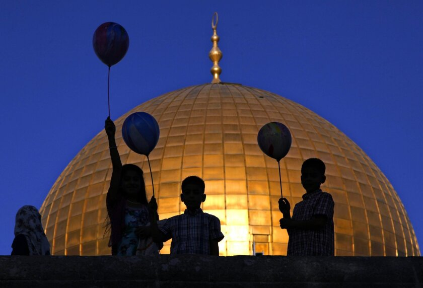 FILE - In this Thursday, Sept. 24, 2015 file photo, Palestinian children hold balloons during the Muslim holiday of Eid al-Adha, near the Dome of the Rock Mosque in the Al Aqsa Mosque compound in Jerusalem's Old City. Video surveillance of the Holy Land's most sensitive shrine was meant to be a quick fix for lowering tensions that have driven months of Israeli-Palestinian violence, but disputes over who would controls the footage and what it could show appear to be holding up the installation of the cameras. (AP Photo/Mahmoud Illean, File)