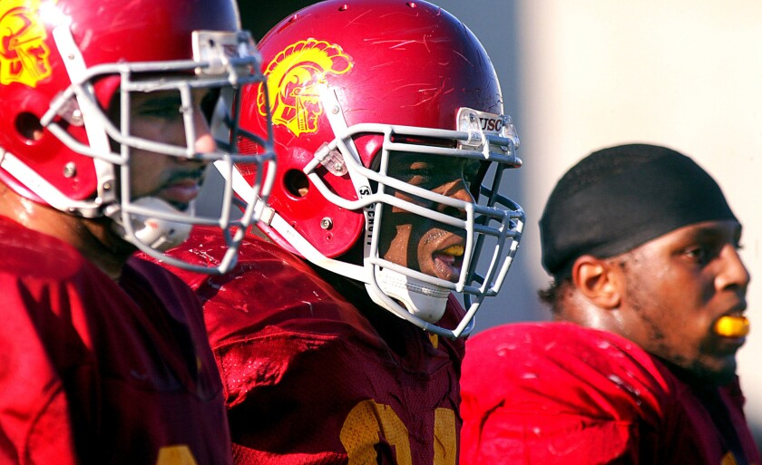 Former Trojan Keneche Udeze, center, has been hired to be USC's defensive line coach.