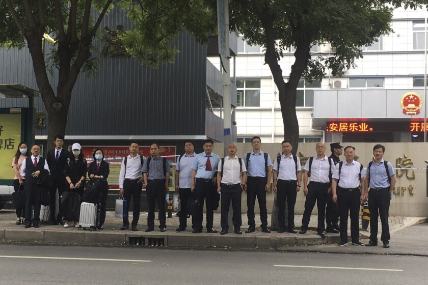 In this photo released by the defendants legal team, a team of lawyers for defendants on trial that included prominent Chinese pig farmer Sun Dawu stand outside the courthouse in Gaobeidian, in Northern China's Hebei province on Friday, 16 July 2021. The prominent Chinese pig farmer who was detained after praising lawyers during a crackdown on legal activists by President Xi Jinping's government went on trial Thursday, July 15, 2021 on charges including fighting with police and organizing a protest, defense lawyers said. (Defendants legal team via AP)