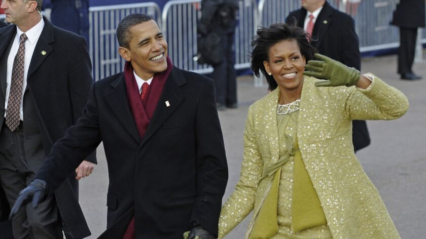 Then-President Obama and Michelle Obama walk the inauguration parade route after his swearing-in in 2009.