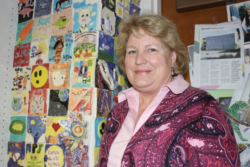Susan Walters stands with tiles her students have made in her Gillespie School art room.